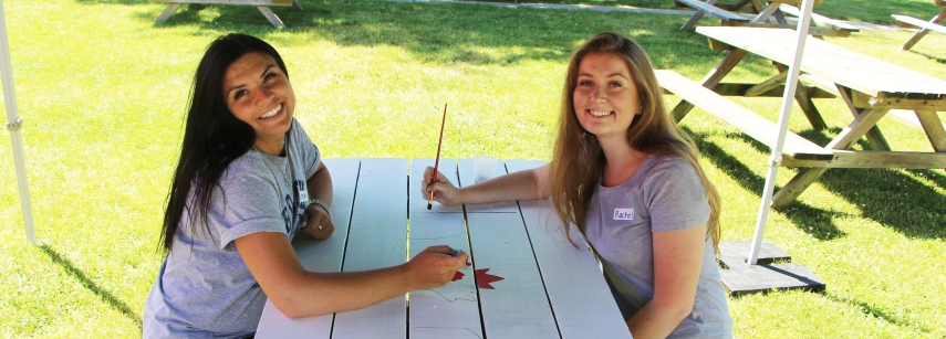 Two girls painting a picnic table for Canada day