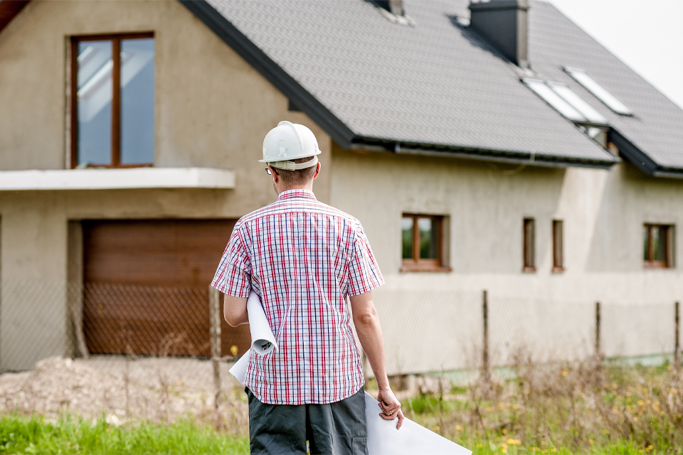 man walking towards unfinished hous with plans and hard hat on