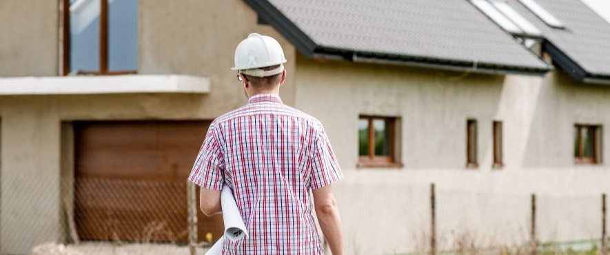 man walking towards unfinished house with plans under arm and hard hat on