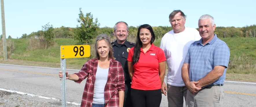 people standing next to farm 911 sign on road