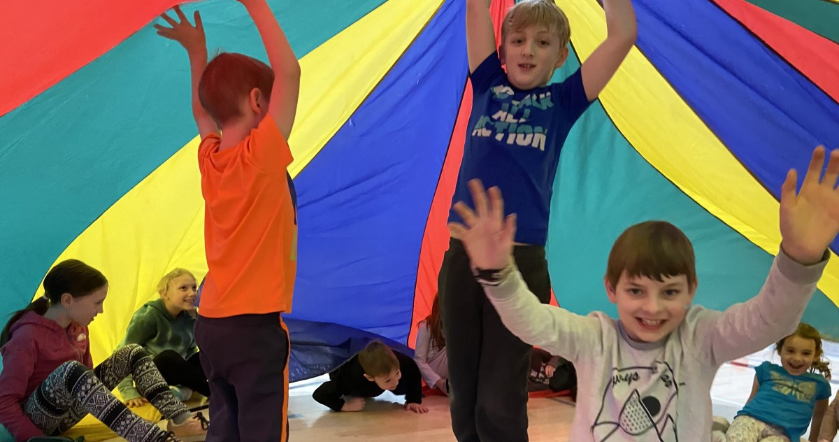 children underneath rainbow coloured parachute