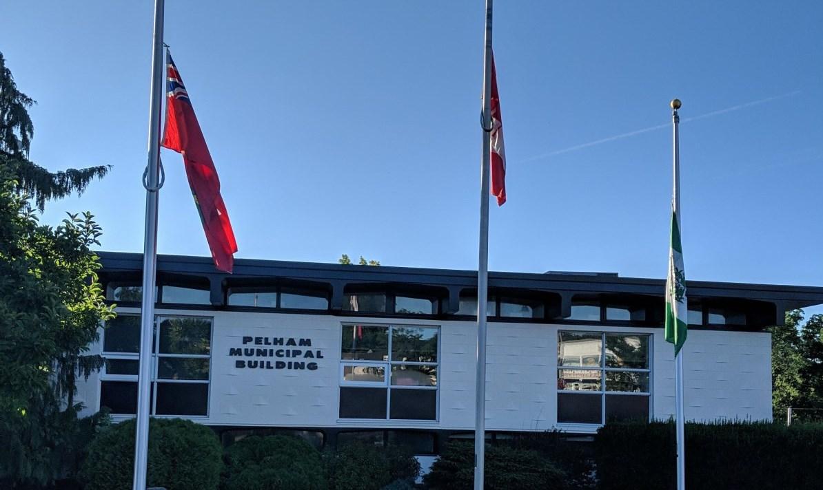 flags at town hall flying at half mast
