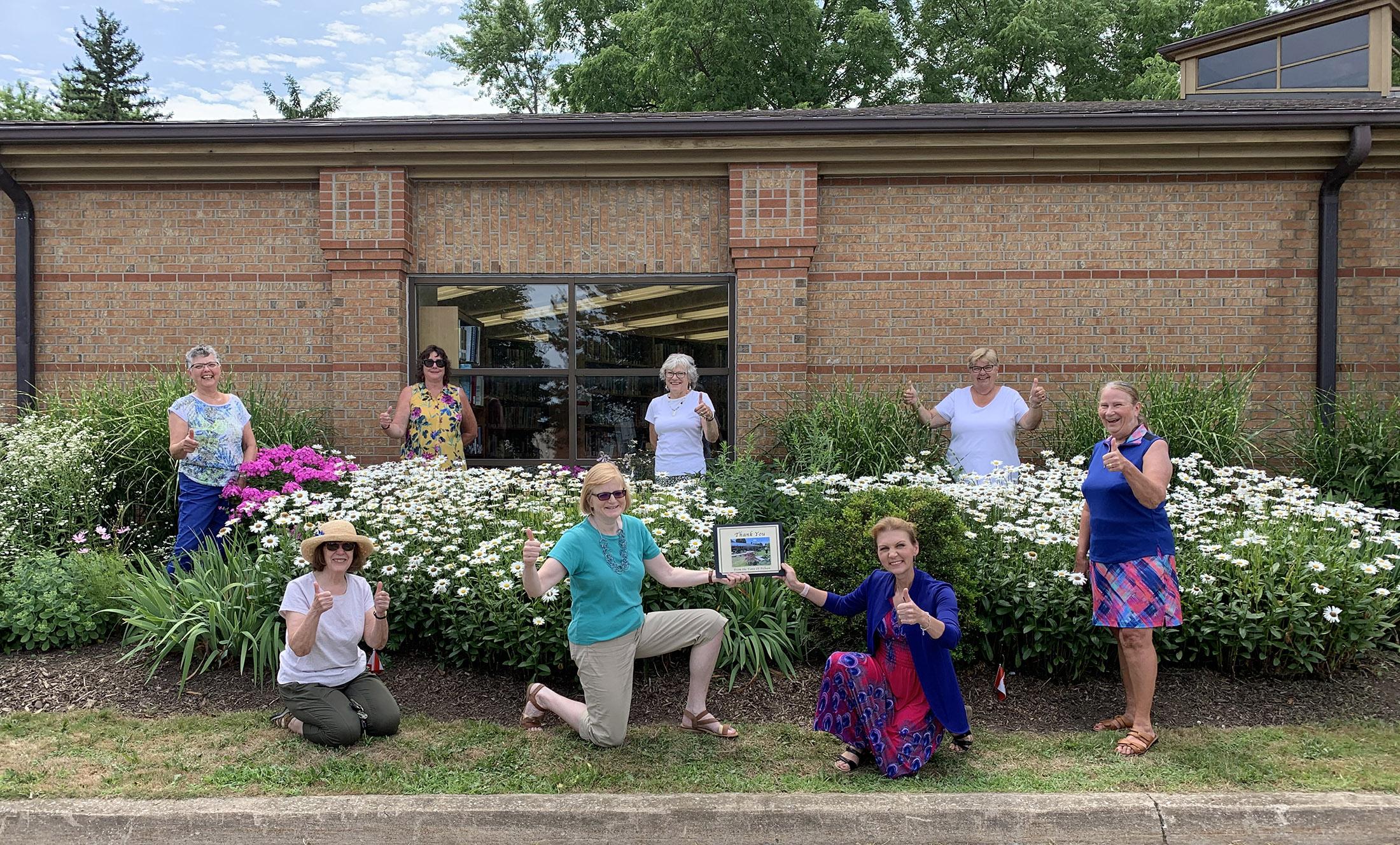 garden club members posing in garden