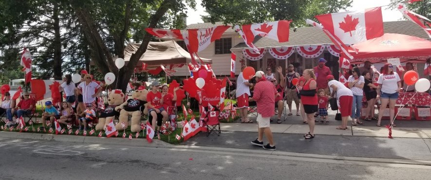 people dressed in red and white gathering on driveway to celebrate canada day