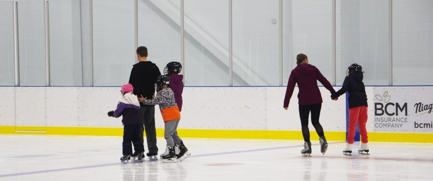 family skating on indoor ice rink
