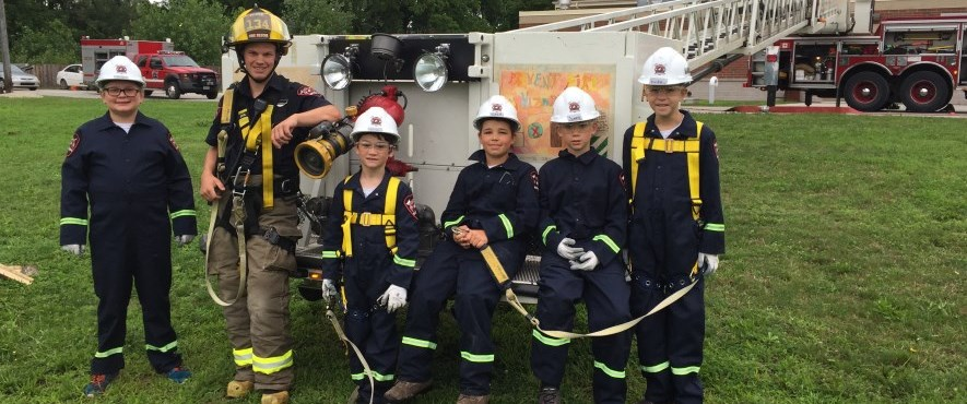 kids dressed as firefighters with one adult firefighter during camp