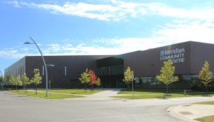 exterior of meridian community centre, trees and grass