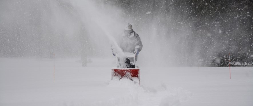 person snowblowing during storm